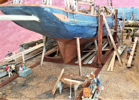 Dandy Score Shipyard model - Shipwrights repairing rudder. Local youths look on. Yard hand loading planks into steam box